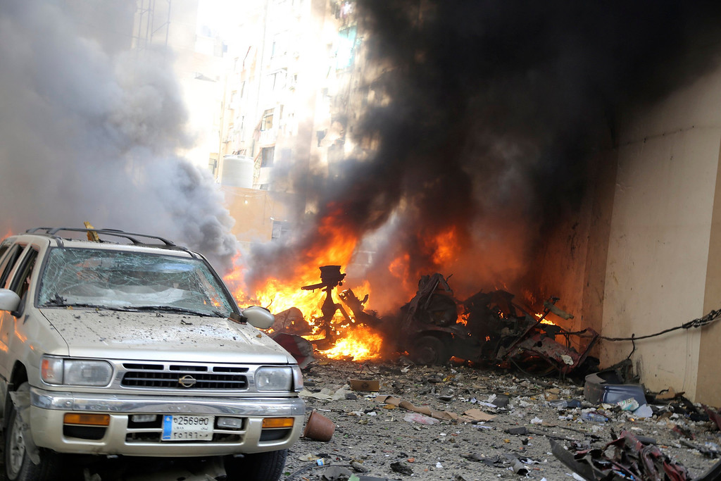 . Smoke rises as damaged and burning vehicles are seen at the site of an explosion in Beirut\'s southern suburbs, July 9, 2013.  REUTERS/Issam Kobeisi