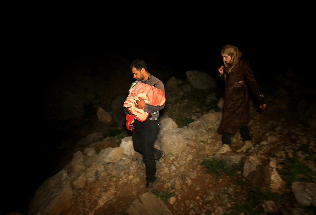 . In this picture taken late Saturday April 19, 2014, a Syrian man carries his newborn baby in his arms, left, as he and his wife, right, descend a mountain path from the 2,814-meter (9,232-foot) high Mount Hermon (Jabal el-Sheikh), into the town of Chebaa in southeast Lebanon. Violence forced them to flee their home in the Syrian village of Beit Jinn, near the Israeli-occupied Golan Heights. The group of Syrians that reached Chebaa at sunrise on Sunday joined more than 1 million other Syrian refugees inside Lebanon. (AP Photo/Hussein Malla)