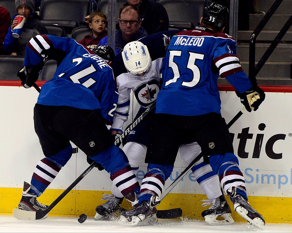 . Marc-Andre Cliche (24) of the Colorado Avalanche and Cody McLeod (55) sandwich Anthony Peluso (14) of the Winnipeg Jets during the first period of action.  (Photo by AAron Ontiveroz/The Denver Post)