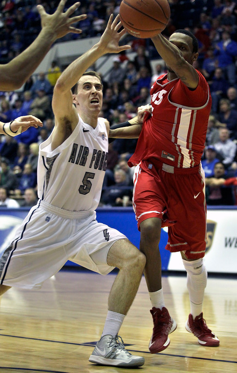 . Air Force\'s Mike Fitzgerald, left, blocks a pass by an unidentified New Mexico player during the first half of an NCAA college basketball game in Air Force Academy, Colo., Saturday, March 9, 2013. (AP Photo/Brennan Linsley)