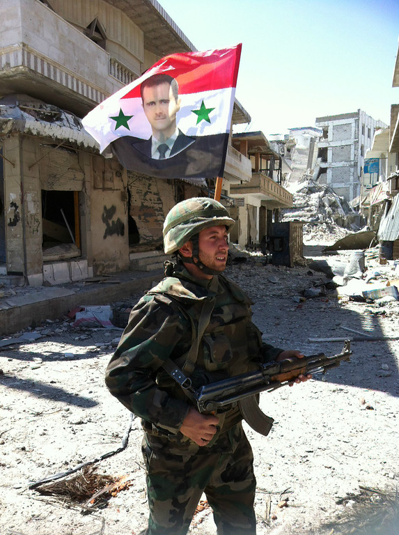 . A Syrian army\'s soldier walks in a street left in ruins with a national flag featuring Syria\'s President Bachar al-Assad on June 5, 2013 in the city of Qusayr in Syria\'s central Homs province, after the Syrian government forces seized total control of the city and the surrounding region. The Syrian army ousted rebels from the strategic town of Qusayr after a blistering 17-day assault led by Hezbollah fighters, scoring a major battlefield success in a war that has killed at least 94,000 people.   AFP PHOTO / STR-/AFP/Getty Images
