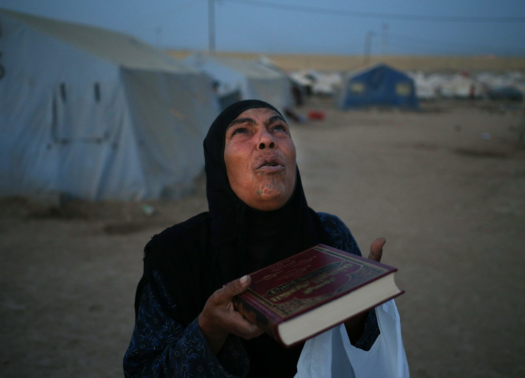 . An Iraqi displaced woman who fled with her family from the Iraqi northern city of Mosul, prays, after receiving a copy of the Quran, Islam\'s holy book and prayer carpet,  from a Kurdish local charity organization, a day before the start of the Islamic holy month of Ramadan, at a camp for displaced Iraqis who fled from Mosul and other towns, in Khazer area outside Irbil north Iraq, Saturday, June 28, 2014. Across a wide belt that stretches halfway around the globe, the worldís estimated 1.6 billion Muslims will mark the beginning of Ramadan this weekend. The holy season is marred by unprecedented turmoil, violence and sectarian hatreds that threaten to rip apart the Middle East, the epicenter of Islam. (AP Photo/Hussein Malla)