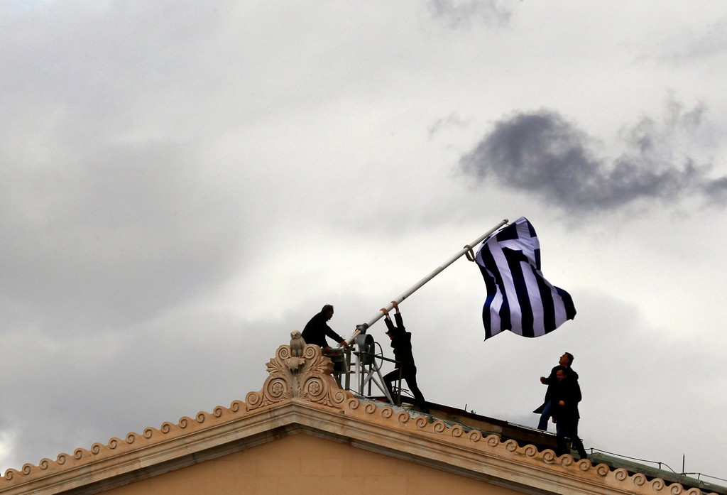 . Greek parliament employees raise a mast after they replaced torn-off Greek flag with a new one atop the parliament in Athens Syntagma (Constitution) square April 18, 2012.Greeks go to the polls in about two weeks and at stake is Greece\'s willingness to impose harsh measures and exit the crisis. The winner(s) must convince international lenders that there will be no relaxing of austerity policies and reforms or risk bailout installments needed to keep Greece afloat. REUTERS/Yannis Behrakis