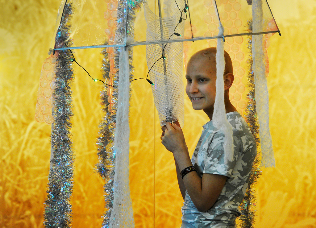 Description of . AURORA, CO - OCTOBER 31: This young man caught my eye during a Halloween party at Children's Hospital in Aurora Colorado this year. Cancer patient, Izaac Kinnison, 11, holds a clear umbrella with strands of tinsel and lights on it depicting a jelly fish during a Halloween party at Children's Hospital Colorado on the Anschutz Medical Campus in Aurora Colorado, Thursday afternoon, October 31, 2013.  Kinnison is fighting a brain tumor and is currently going through a round of chemotherapy at Children's, but found the strength to come to the party. (Photo By Andy Cross/The Denver Post)