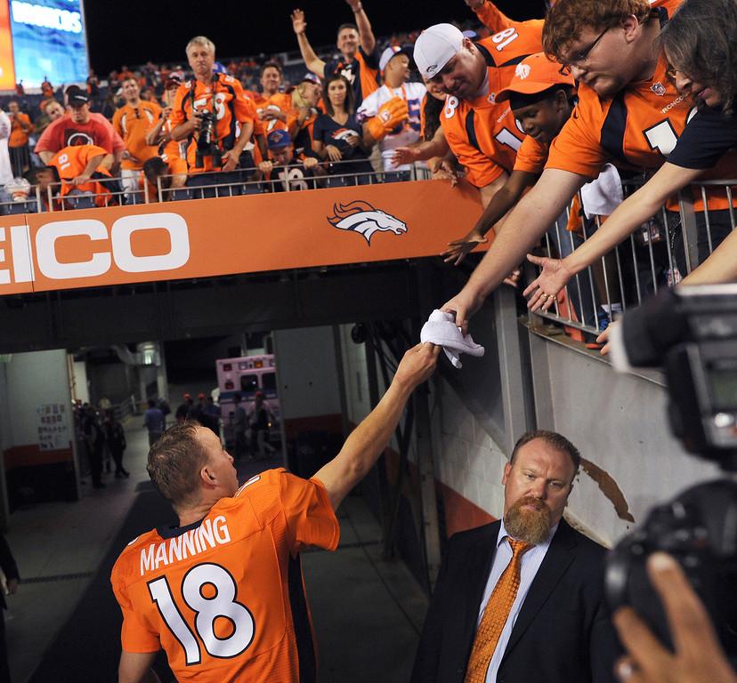 . Denver Broncos quarterback Peyton Manning (18) greets fans after the Broncos defeated the Ravens 49-24 in Denver.   (Photo by Joe Amon/The Denver Post)