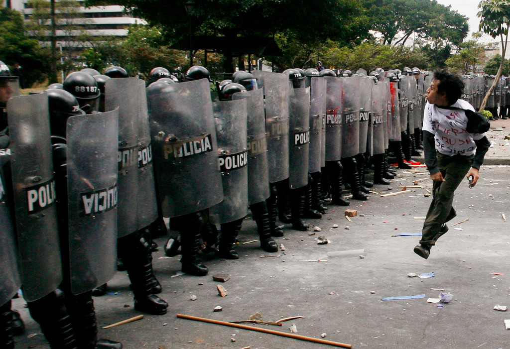 . A Colombian demonstrator clashes with anti-riot police after the arrival of U.S. President George W. Bush in Bogota, Colombia, March 11, 2007.  REUTERS/Daniel Munoz