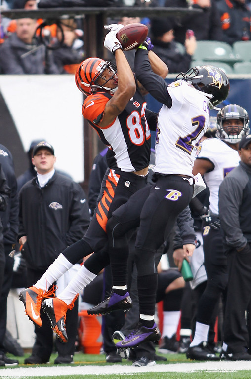 . Corey Graham #24 of the Baltimore Ravens takes the football away from Marvin Jones #82 of the Cincinnati Bengals for an interception during their game at Paul Brown Stadium on December 29, 2013 in Cincinnati, Ohio.  (Photo by John Grieshop/Getty Images)