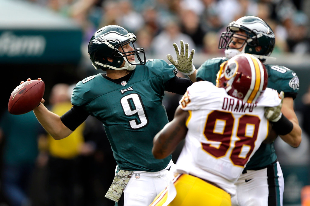 . Philadelphia Eagles quarterback Nick Foles (9) passes the ball under pressure from Washington Redskins outside linebacker Brian Orakpo during the first half of an NFL football game in Philadelphia, Sunday, Nov. 17, 2013. (AP Photo/Matt Rourke)