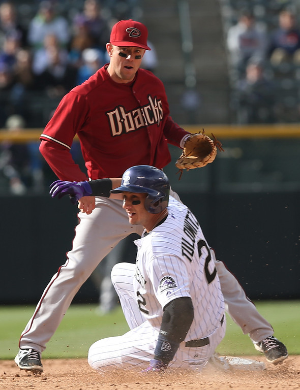 . Arizona Diamondbacks second baseman Aaron Hill, back, forces out Colorado Rockies\' Troy Tulowitzki at second base on the front end of a double play hit into by Wilin Rosario in the ninth inning of the Diamondbacks\' 5-3 victory in a baseball game in Denver on Sunday, April 6, 2014. (AP Photo/David Zalubowski)