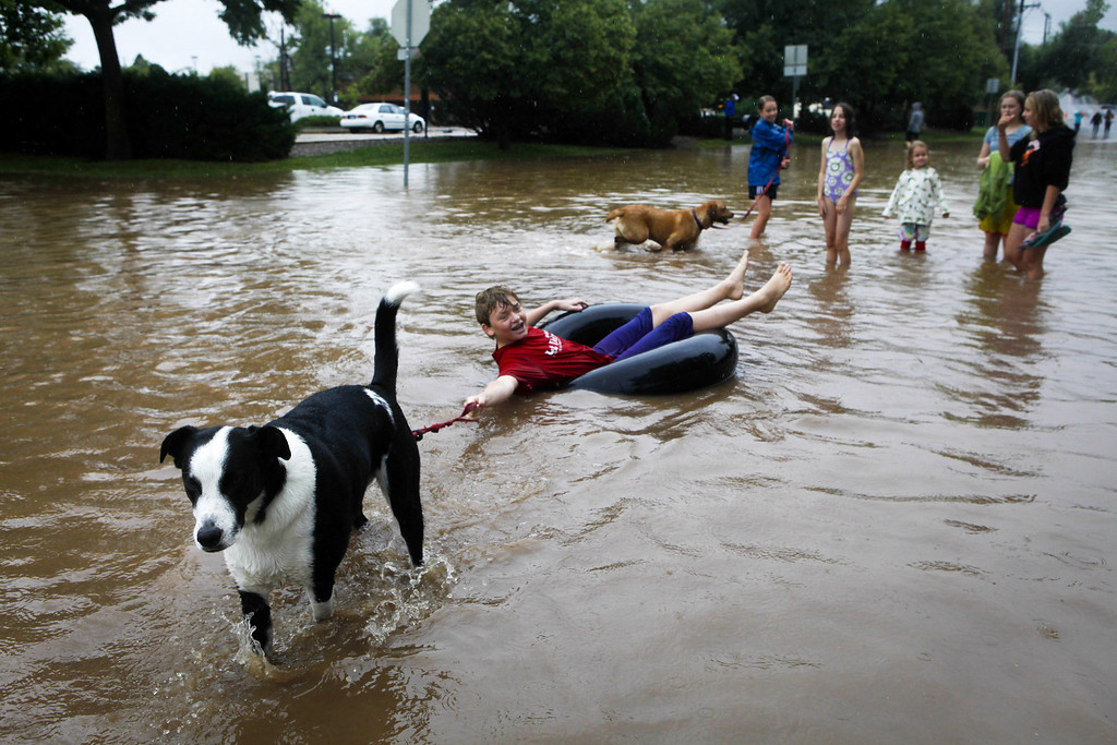 . BOULDER, CO - SEPTEMBER 12: Nicky Toor, 15, is pulled by his dog Chaco down Ninth Street alongside North Boulder Park September 12, 2013 in Boulder, Colorado. An estimated 6-10 inches of rain fell in 12-18 hours and more is expected throughout the day. Flash flood sirens warned people to stay away from Boulder Creek and seek higher ground.  (Photo by Dana Romanoff/Getty Images)