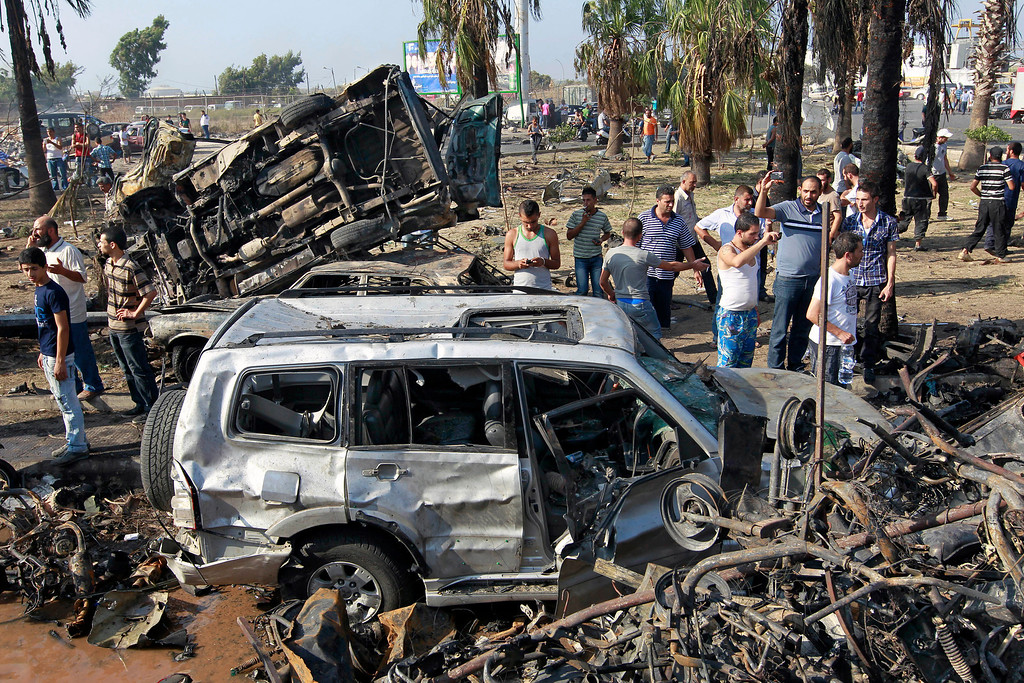 . People gather outside the Al-Taqwa mosque amid charred cars and wide damage, in the northern city of Tripoli, Lebanon, Friday Aug. 23, 2013.  (AP Photo/Bilal Hussein)
