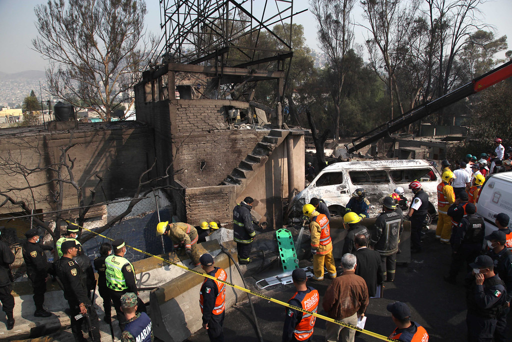 . Firefighters work next to destroyed houses and vehicles after a gas tanker truck exploded on a nearby highway in the Mexico City suburb of Ecatepec early Tuesday, May 7, 2013. The blast killed and injured dozens, according to the Citizen Safety Department of Mexico State. Officials did not rule out the possibility the death toll could rise as emergency workers continued sifting through the charred remains of vehicles and homes built near the highway on the northern edge of the metropolis. (AP Photo/Marco Ugarte)