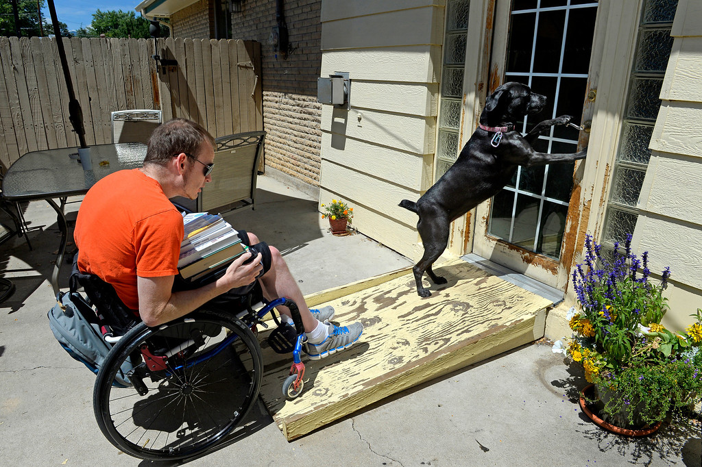 """. LuLu opens a patio door for James, loaded down with school books. She immediately licked his injured legs when he came home from the hospital. \""""It was weird, she knew right away... She got me through a lot of this.\"""" (Photo By Craig F. Walker / The Denver Post)"""