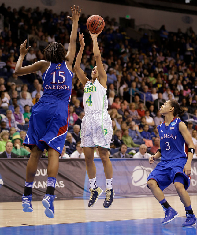 . Notre Dame guard Skylar Diggins (4) takes a shot over Kansas forward Chelsea Gardner (15) as guard Angel Goodrich (3) watches during the second half of a regional semi-final of an NCAA college basketball tournament Sunday March 31, 2013 in Norfolk, Va. Notre Dame won 93-63.  (AP Photo/Steve Helber)