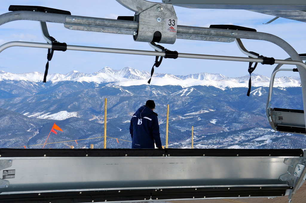 . A Breckenridge Ski Resort empolyee helps put the finishing touches on the new Kensho six-passenger lift atop the Peak 6 expansion scheduled to open at noon on Christmas day. The slopes of Keystone Resort can be seen in he distance. Scott Willoughby, The Denver Post
