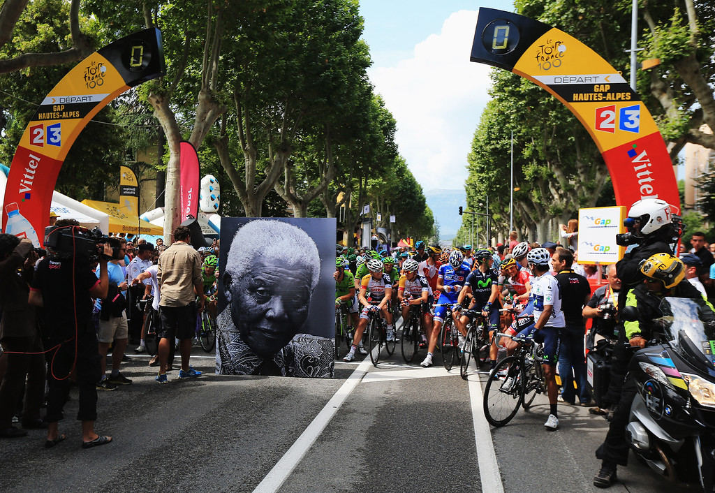 . GAP, FRANCE - JULY 18:  The peloton waits behind a large picture commemorating the birthday of former South African President Nelson Mandela before stage eighteen of the 2013 Tour de France, a 172.5KM road stage from Gap to l\'Alpe d\'Huez, on July 18, 2013 in Gap, France.  (Photo by Doug Pensinger/Getty Images)
