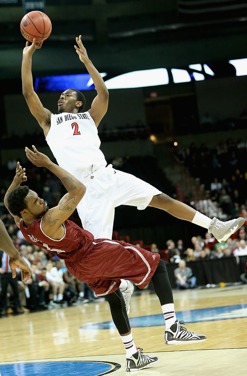 . Xavier Thames #2 of the San Diego State Aztecs goes up for a shot over Ian Baker #4 of the New Mexico State Aggies during the second round of the 2014 NCAA Men\'s Basketball Tournament at Spokane Veterans Memorial Arena on March 20, 2014 in Spokane, Washington.  (Photo by Stephen Dunn/Getty Images)