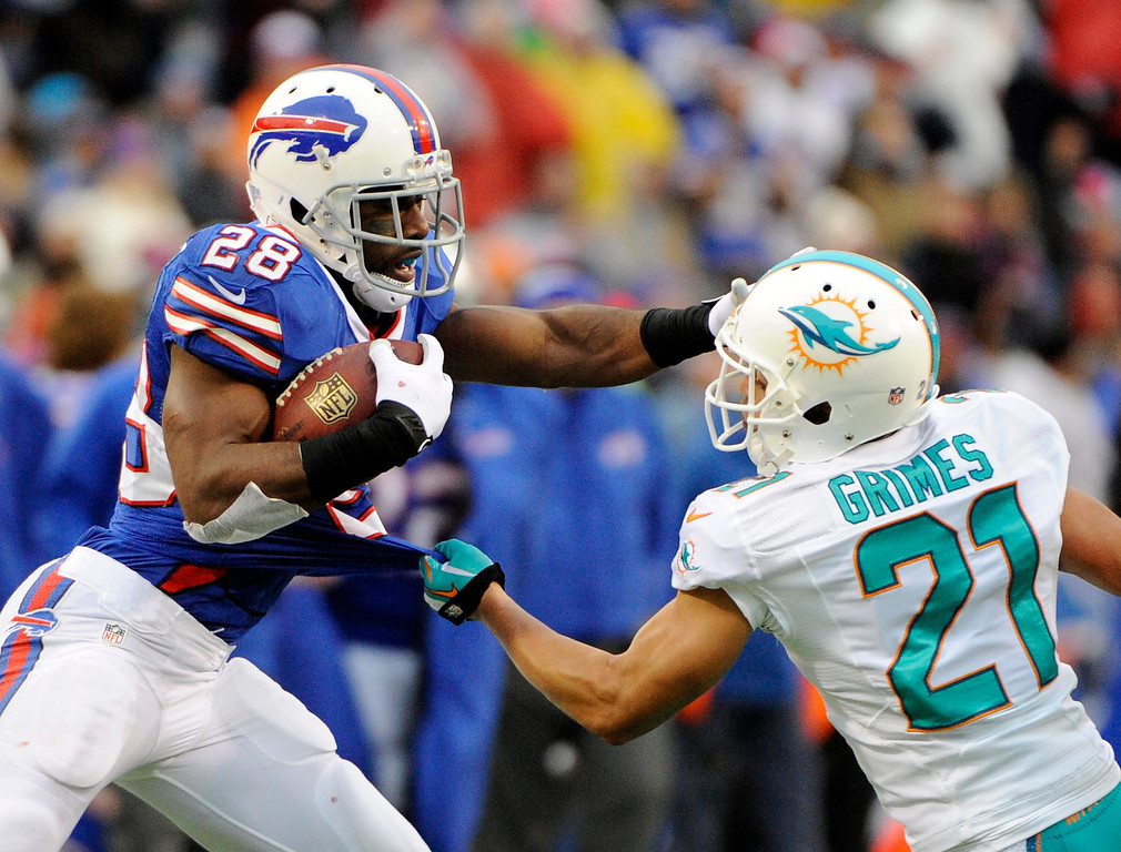 . Buffalo Bills running back C.J. Spiller (28) straight-arms Miami Dolphins cornerback Brent Grimes (21) during the second half of an NFL football game on Sunday, Dec. 22, 2013, in Orchard Park, N.Y. (AP Photo/Gary Wiepert)