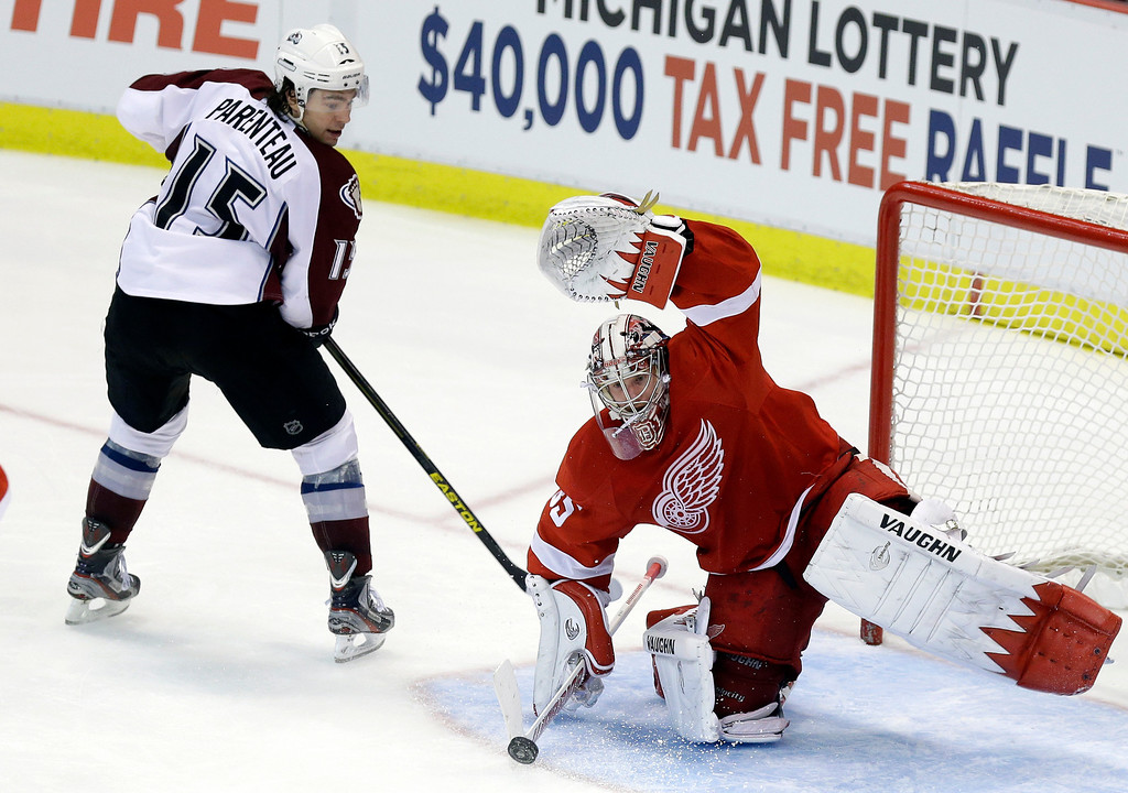 . Detroit Red Wings goalie Jimmy Howard (35) deflects a shot by Colorado Avalanche right wing P.A. Parenteau (15) during the third period of an NHL hockey game in Detroit, Tuesday, March 5, 2013. Detroit won 2-1. (AP Photo/Carlos Osorio)