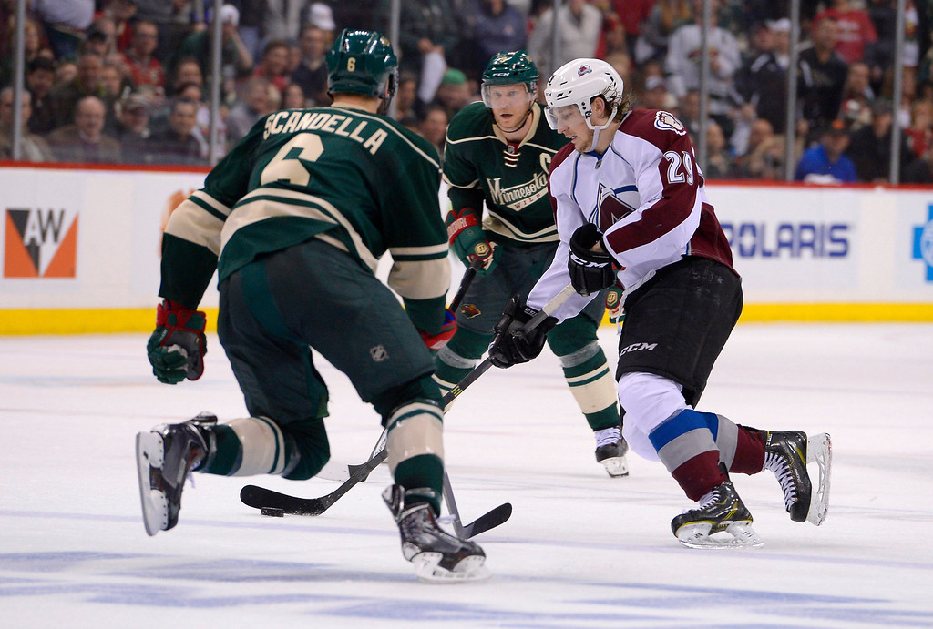 . Colorado Avalanche center Nathan MacKinnon (29) skates the puck between Minnesota Wild center Mikko Koivu (9) and Minnesota Wild defenseman Marco Scandella (6) late in the third period April 24, 2014 in Game 4 of the Stanley Cup Playoffs at Xcel Energy Center.   (Photo by John Leyba/The Denver Post)