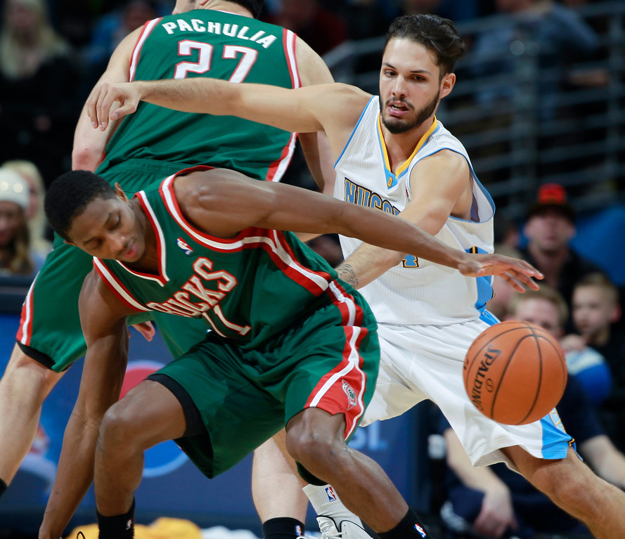 . Milwaukee Bucks guard Brandon Knight, front, reaches out for loose ball as Denver Nuggets guard Evan Fournier, of France, covers in the fourth quarter of the Nuggets\' 110-100 victory in an NBA basketball game in Denver on Wednesday, Feb. 5, 2014. (AP Photo/David Zalubowski)