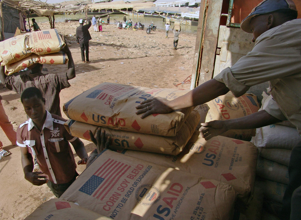. Men transport humanitarian food aid onto small flat bottom boats at Mopti in this February 4, 2013 file photo. A White House plan to modernize the major U.S. Food aid program, by donating cash rather than American-grown food, is in trouble after fierce lobbying by farm groups, food processors, shippers and others who set out to sink the idea months before it was unveiled in President Barack Obama\'s fiscal 2014 budget.   REUTERS/Alain Amontchi