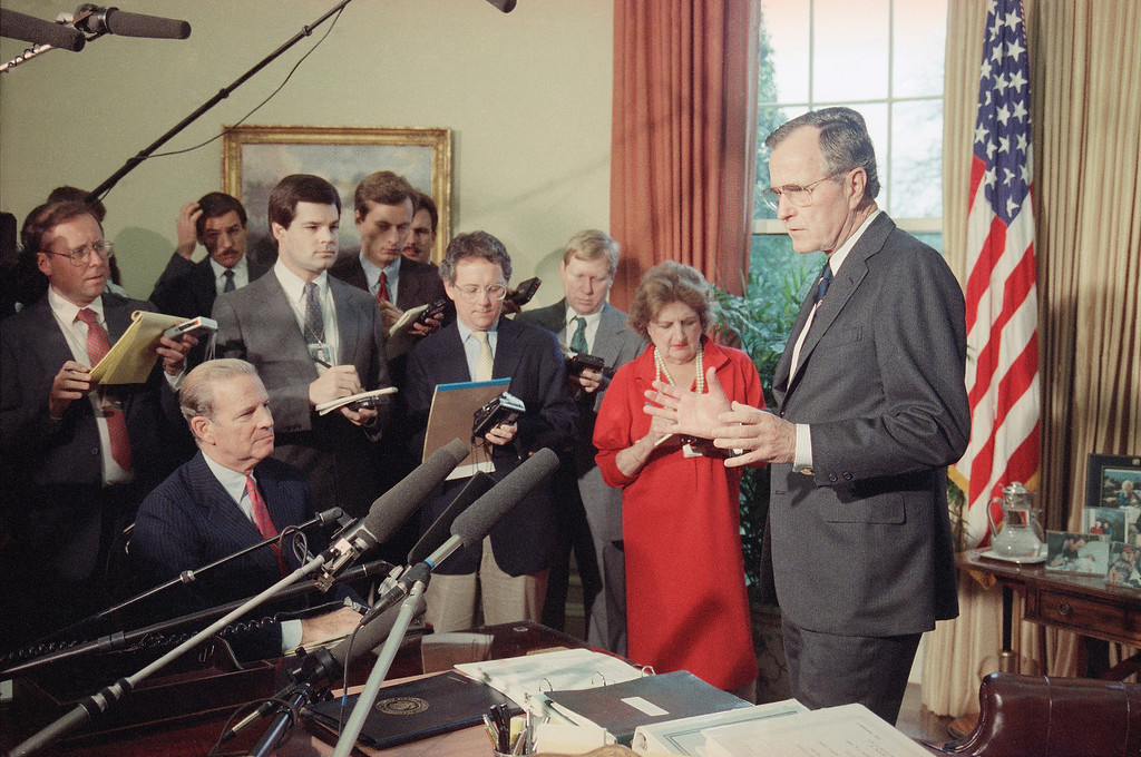 . President  George H. Bush, with Secretary of State James Baker III, seated looking on left, tell members of the press on Tuesday, Nov. 29, 1989, in the Oval Office of the White House in Washington of his agenda at the upcoming summit in Malta this weekend.   Bush insists his shipboard summit with Soviet President Mikhail S. Gorbachev will yield no deals and no surprises. Reporter Helen Thomas in red dress at right.  (AP Photo/Barry Thumma)