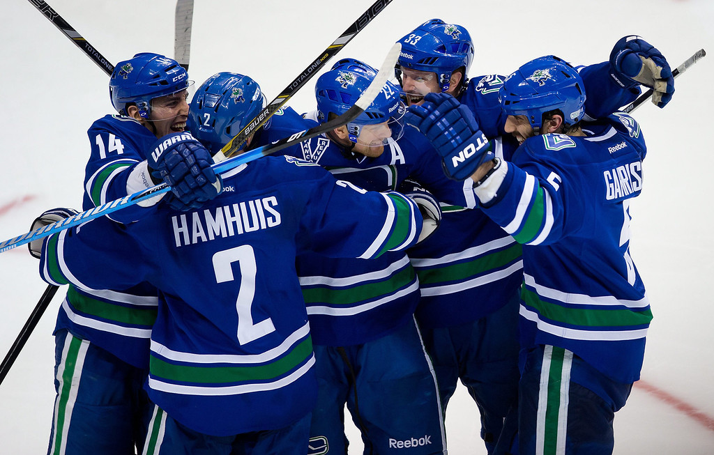 . Vancouver Canucks\' Alex Burrows; Dan Hamhuis; Daniel Sedin, of Sweden; Henrik Sedin, of Sweden; and Jason Garrison celebrate Daniel Sedin\'s goal against the Colorado Avalanche during the third period of an NHL hockey game in Vancouver, British Columbia, on Thursday, March 28, 2013. (AP Photo/The Canadian Press, Darryl Dyck)