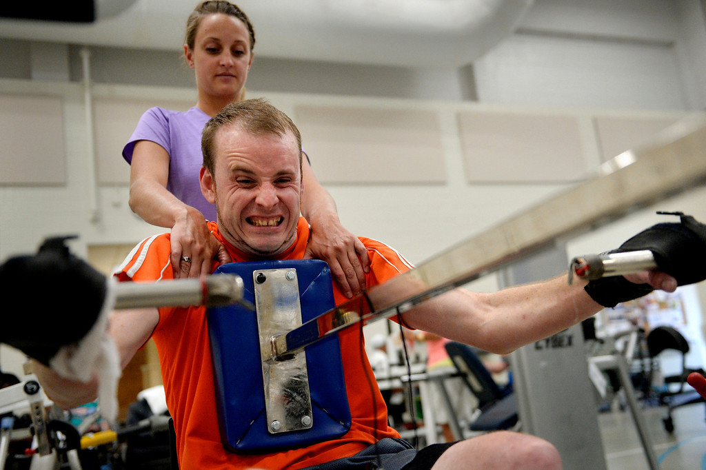 """. Therapist Shelby Allen helps James on one of Craig\'s weight machines, each designed to be easily accessible to injured clients. \""""I originally gave myself three and a half years to be functional, to walk around the house with crutches, to get out of the chair. So I\'ve got a year and a half. I believe it will happen. I will not be in that damn chair.\"""" (Photo By Craig F. Walker / The Denver Post)"""