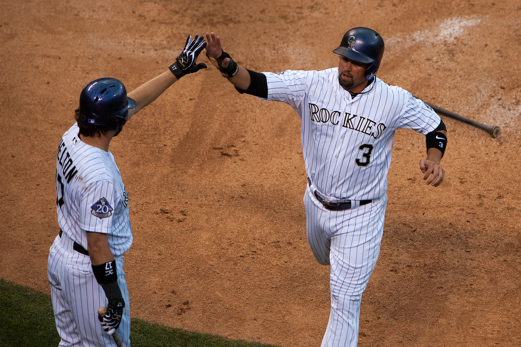 . DENVER, CO - JULY 4:  Michael Cuddyer #3 of the Colorado Rockies is congratulated by Todd Helton #17 after Cuddyer scored in the third inning of a game against the Los Angeles Dodgers at Coors Field on July 4, 2013 in Denver, Colorado.  The Rockies beat the Dodgers 9-5. (Photo by Dustin Bradford/Getty Images)
