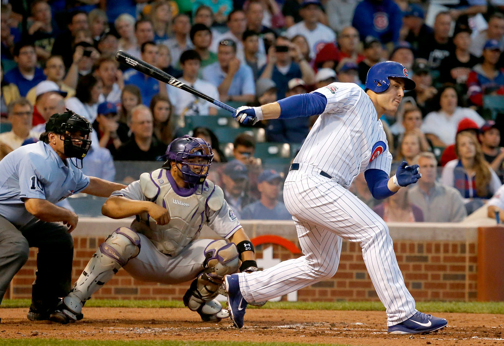 . Chicago Cubs\' Anthony Rizzo hits an RBI single off Colorado Rockies starting pitcher Jorge De La Rosa, scoring Emilio Bonifacio, as catcher Wilin Rosario and home plate umpire Phil Cuzzi watch, during the first inning of a baseball game Tuesday, July 29, 2014, in Chicago. (AP Photo/Charles Rex Arbogast)