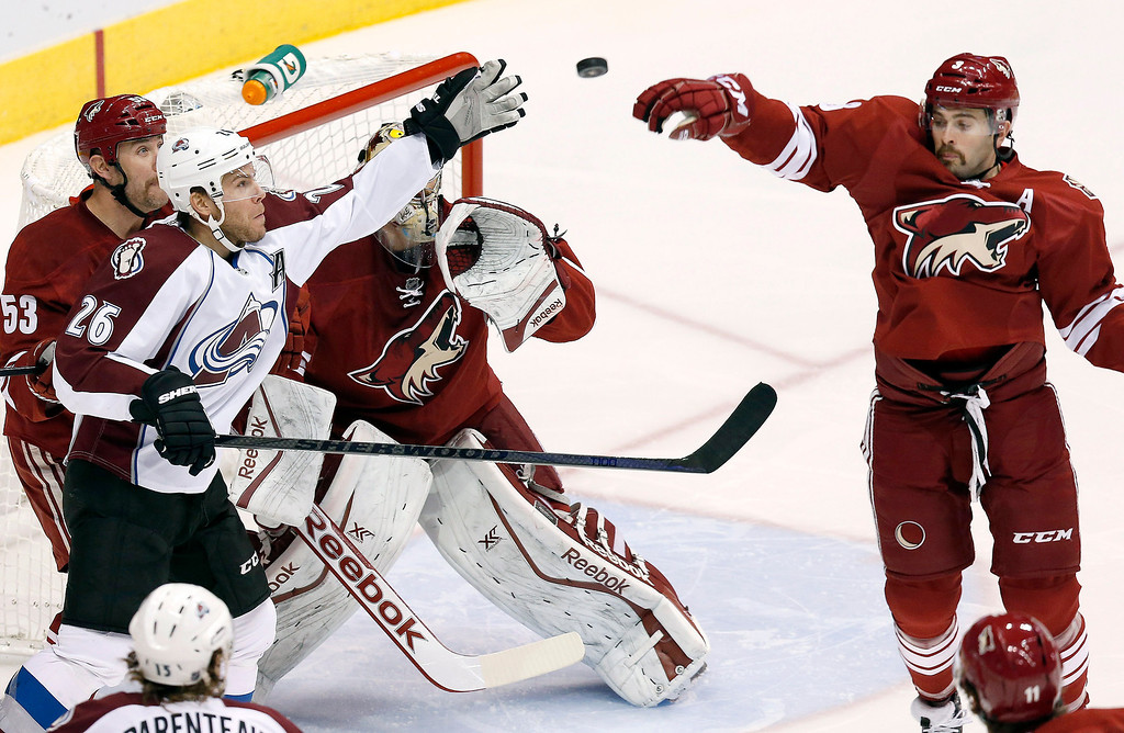 . Colorado Avalanche\'s Paul Stastny (26) and Phoenix Coyotes\' Keith Yandle, right, reach out to catch the puck as Coyotes\' Derek Morris (53) and Mike Smith stand by during the first period of an NHL hockey game Thursday, Nov. 21, 2013, in Glendale, Ariz. (AP Photo/Ross D. Franklin)