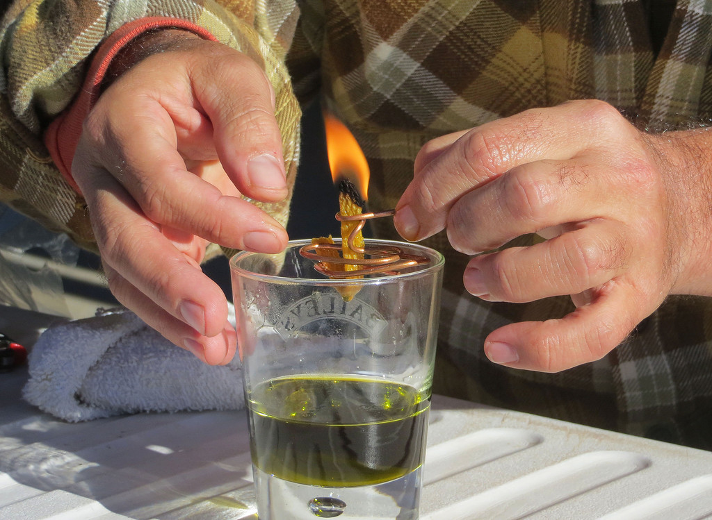 . In this Oct. 5, 2013 photo, Derek Cross, a chef who specializes in cooking with hemp, demonstrates the burning properties of hemp oil, which he touts as a digestible bio fuel, during the first known harvest of industrial hemp in the U.S. since the 1950s, at a farm in Springfield, Colo. America is one of hempís fastest-growing markets, with imports largely coming from China and Canada. Most of that is hemp seed and hemp oil, which finds its way into granola bars, soaps, lotions and even cooking oil. (AP Photo/Kristen Wyatt)