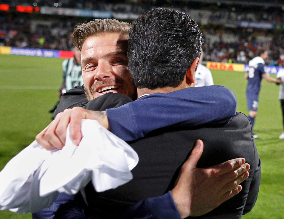 . Paris Saint-Germain\'s David Beckham (L) hugs owner of Qatari TV channel Al Jazeera Sport and PSG club owner Nasser Al-Khelaifi at the end of their team\'s French Ligue 1 soccer match against Olympique Lyon at the Gerland stadium in Lyon May 12, 2013. Paris Saint-Germain secured the French Ligue 1 soccer Championships title after beating Olympique Lyon 0-1 on Sunday in Lyon.        REUTERS/Robert Pratta