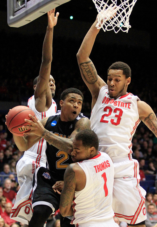. Iona guard Lamont Jones (2) is defended by Ohio State forward Sam Thompson, center Amir Williams (23), and forward Deshaun Thomas (1) in the first half of a second-round game at the NCAA college basketball tournament, Friday, March 22, 2013, in Dayton, Ohio. (AP Photo/Skip Peterson)