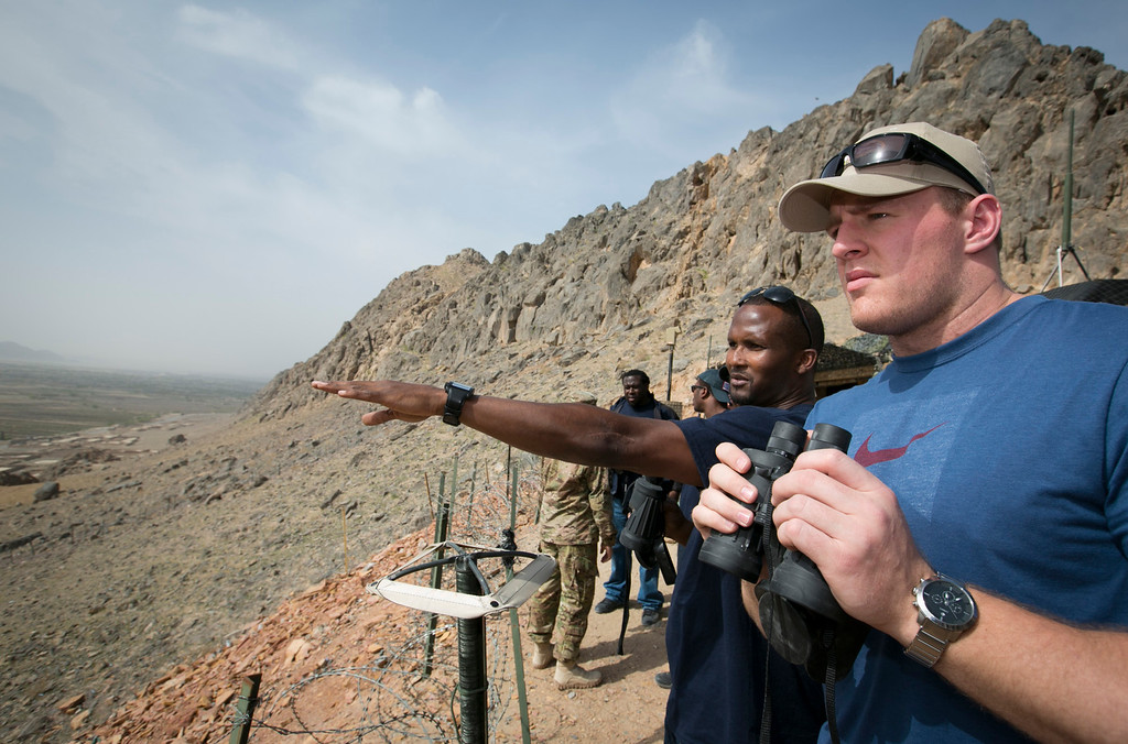 . Denver Broncos cornerback Champ Bailey (L) and Houston Texans defensive end J.J. Watt  look out from a mountaintop military base in the Middle East during a stop on their week-long USO/NFL tour March 18, 2013. This is the first USO tour for Bailey and Watt.  USO Photo by Fred Greaves