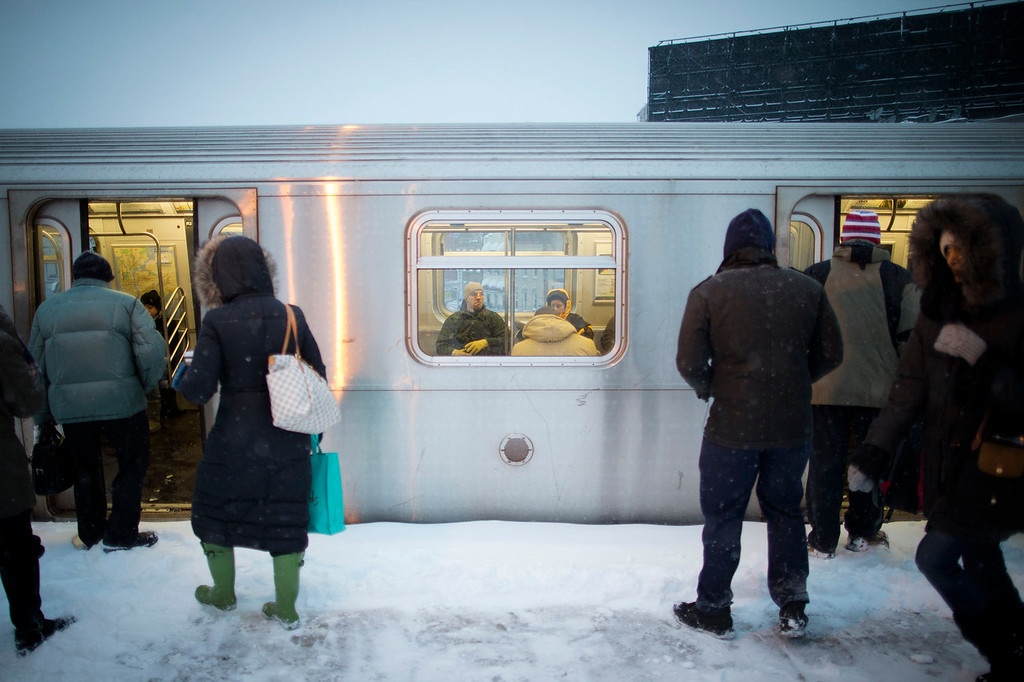 . Commuters brave the wind and snow as they board a train at the Astoria Boulevard subway station, Friday, Jan. 3, 2014, in New York. New York City public schools were closed Friday after up to 7 inches of snow fell by morning in the first snowstorm of the winter. (AP Photo/John Minchillo)
