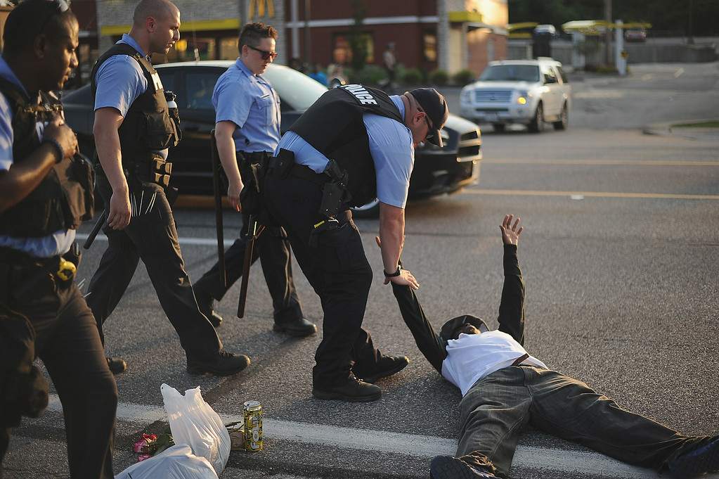 ". A man is arrested after laying in the street while protesting during a peaceful protest on West Florissant Ave. in Ferguson, Missouri on August 19, 2014.  Police in the US city of St. Louis shot dead another suspect on Tuesday, a short distance from a suburb that is the scene of protests over the killing of an unarmed black teenager.  St. Louis Police Chief Sam Dotson said in a tweet that officers had responded to a call and found an apparently agitated man, armed with a knife who yelled ""kill me now\"" and approached the patrol. Michael B. Thomas/AFP/Getty Images"