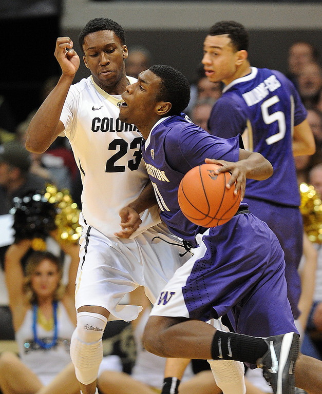 . Mike Anderson, right, of Washington, runs into Jaron Hopkins of Colorado during the first half of an NCAA college basketball game in Boulder, Colo., Sunday, Feb. 9, 2014. (AP Photo/Daily Camera, Cliff Grassmick)