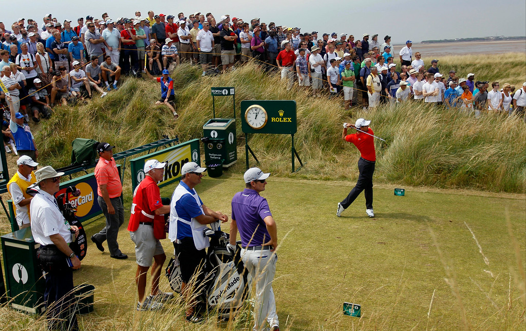 . Adam Scott of Australia plays a shot off the 14th tee as Justin Rose of England, second right, and Jason Dufner of the US, third left , look along the fairway during the second day of the British Open Golf championship at the Royal Liverpool golf club, Hoylake, England, Friday July 18, 2014. (AP Photo/Peter Morrison)