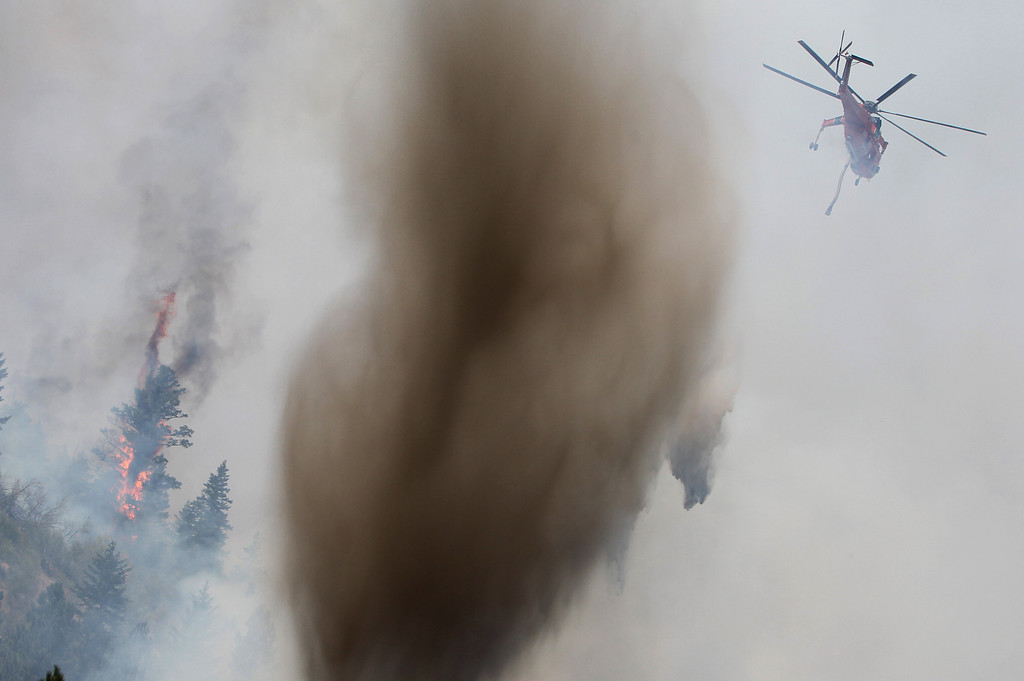 . A helicopter drops muddy water from a nearby pond on the Elk Complex fire in Pine, Idaho on Monday, Aug. 12, 2013. (AP Photo/The Idaho Statesman, Joe Jaszewski)