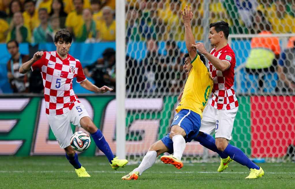 . Brazil\'s Fred, center, falls next to Croatia\'s Dejan Lovren, right, as Croatia\'s Vedran Corluka, left, watches during the group A World Cup soccer match in the opening game of the tournament at Itaquerao Stadium in Sao Paulo, Brazil, Thursday, June 12, 2014. Brazil was awarded a penalty kick after Lovren was issued a yellow card on the play leading to a goal by Brazil\'s Neymar. (AP Photo/Frank Augstein)