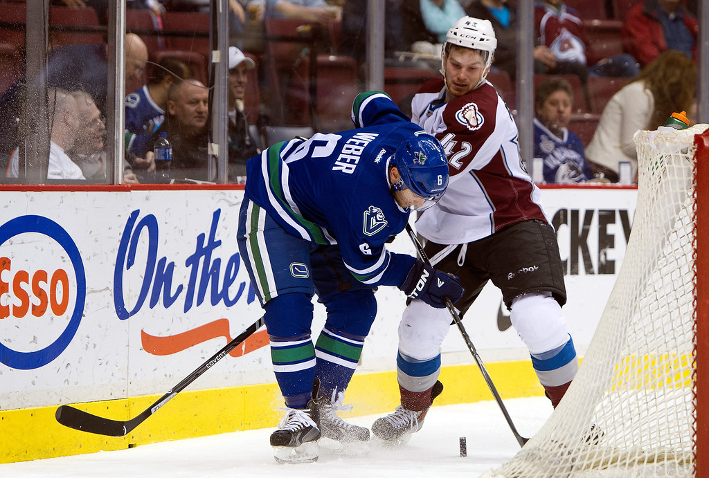 . Yannick Weber #6 of the Vancouver Canucks tries to gain control of the puck while being checked by Brad Malone #42 of the Colorado Avalanche while behind the net during the first period in NHL action on April 10, 2014 at Rogers Arena in Vancouver, British Columbia, Canada.  (Photo by Rich Lam/Getty Images)
