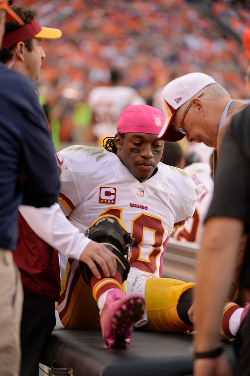 . Washington Redskins quarterback Robert Griffin III (10) is examined on the sidelines after being injured in the fourth quarter.  The Denver Broncos take on the Washington Redskins at Sports Authority Field at Mile High in Denver on October 27, 2013. (Photo by John Leyba/The Denver Post)