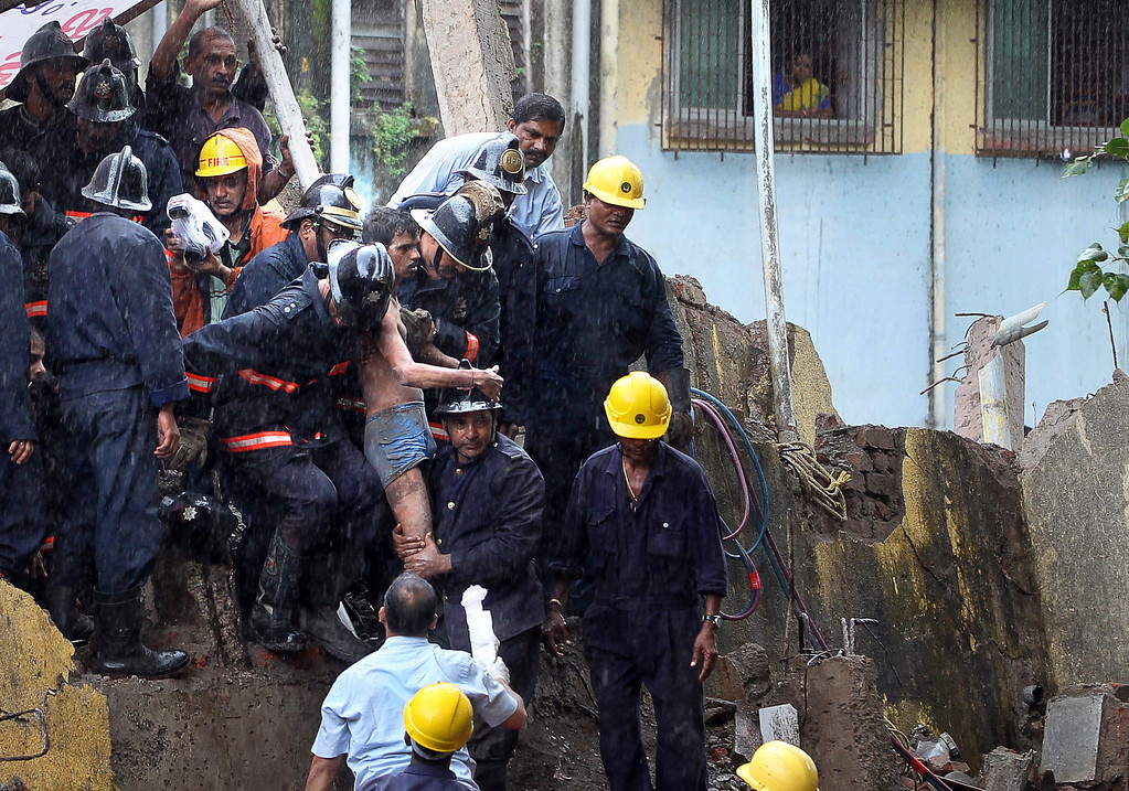 . Indian Fire officials rescue an injured resident from debris of a collapse building in Mumbai, India, Friday, Sept. 27, 2013.  (AP Photo/Rajanish Kakade)