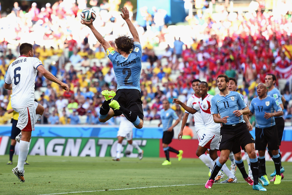. The ball strikes the hand of Diego Lugano of Uruguay on a corner kick during the 2014 FIFA World Cup Brazil Group D match between Uruguay and Costa Rica at Castelao on June 14, 2014 in Fortaleza, Brazil.  (Photo by Laurence Griffiths/Getty Images)