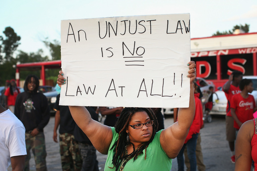 . Demonstrators protest the killing of 18-year-old Michael Brown who was shot by police on Saturday on August 11, 2014 in Ferguson, Missouri. Police responded with tear gas and rubber bullets as residents and their supporters protested the shooting by police of an unarmed black teenager named Michael Brown who was killed Saturday in this suburban St. Louis community. Yesterday 32 arrests were made after protests turned into rioting and looting in Ferguson.  (Photo by Scott Olson/Getty Images)