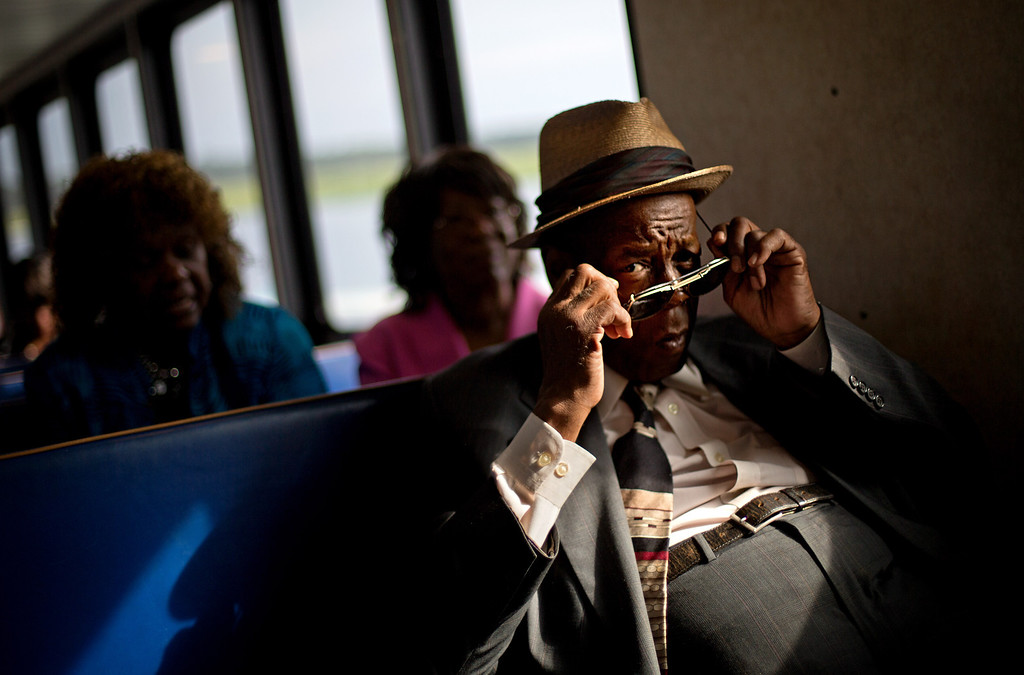 . Eddie Wilson, 65, puts on his glasses while riding the ferry from the mainland to attend a church service for the 129th anniversary of St. Luke Baptist Church on Sapelo Island, Ga. on Sunday, June 9, 2013. (AP Photo/David Goldman)