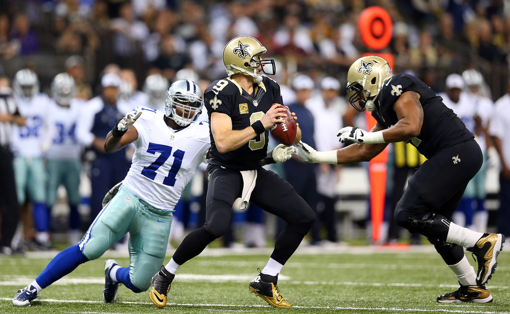 . Quarterback Drew Brees #9 of the New Orleans Saints drops back to pass as defensive end Everette Brown #71 of the Dallas Cowboys defends during a game at the Mercedes-Benz Superdome on November 10, 2013 in New Orleans, Louisiana.  (Photo by Ronald Martinez/Getty Images)