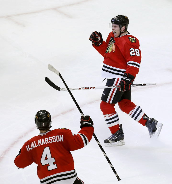. Chicago Blackhawks right wing Ben Smith (28) celebrates his goal with Niklas Hjalmarsson during the second period of an NHL hockey game against the Colorado Avalanche Tuesday, March 4, 2014, in Chicago. (AP Photo/Charles Rex Arbogast)